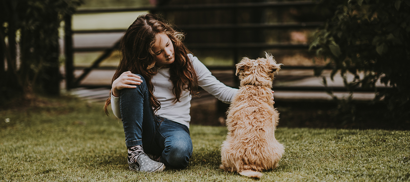 girl petting a dog with dry skin